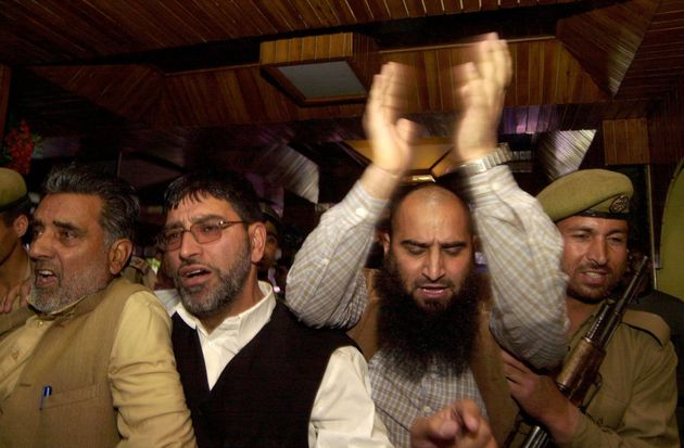 Masrat Alam (second from right) shouts slogans as he is detained by police during a press conference...
