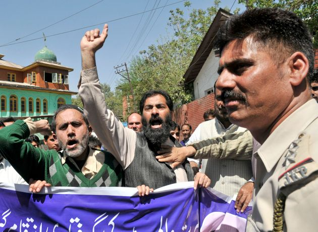 Supporters of Masrat Alam shout slogans during a protest against the slapping of PSA against him on 24...
