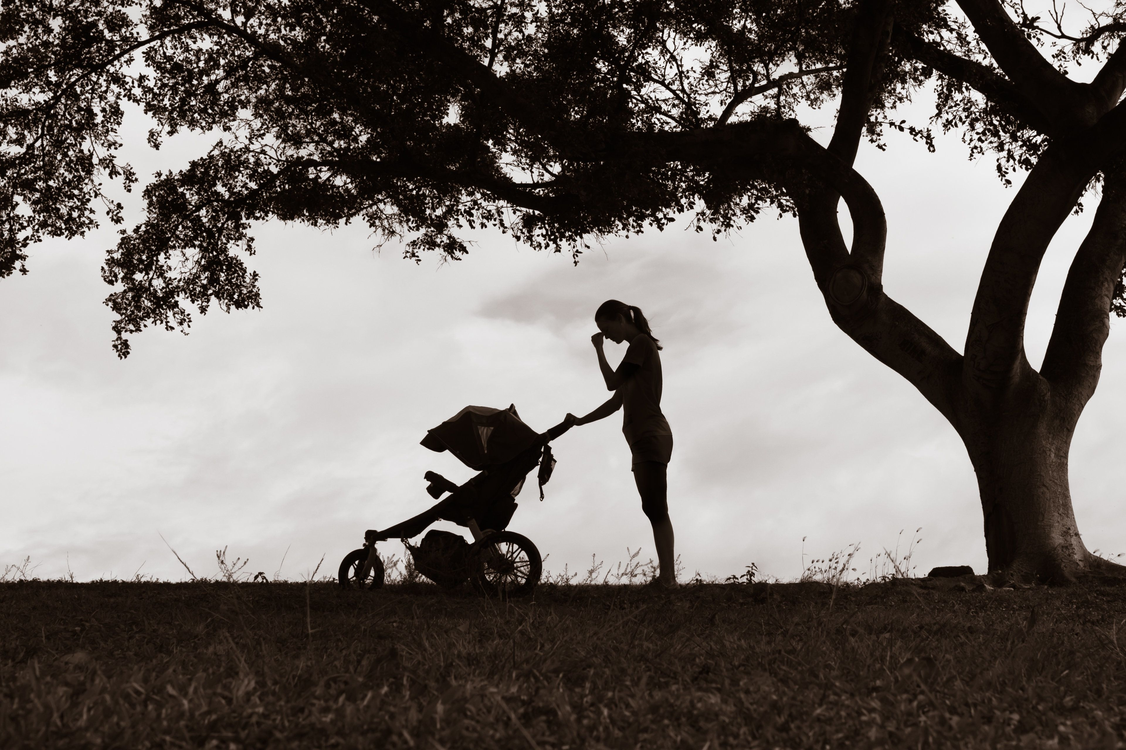 Stressed sad mother pushing stroller.