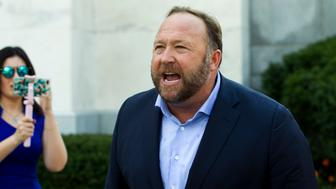 Alex Jones, the right-wing conspiracy theorist, walks the corridors of Capitol Hill, talking to reporters, after listening to Facebook COO Sheryl Sandberg and Twitter CEO Jack Dorsey testify before the Senate Intelligence Committee on 'Foreign Influence Operations and Their Use of Social Media Platforms' on Capitol Hill, Wednesday, Sept. 5, 2018, in Washington. Twitter's permanent ban of conspiracy-monger Alex Jones on Thursday again underscored the difficulty many social-media services face in trying to consistently apply their rules against harassment and other bad behavior. (AP Photo/Jose Luis Magana)