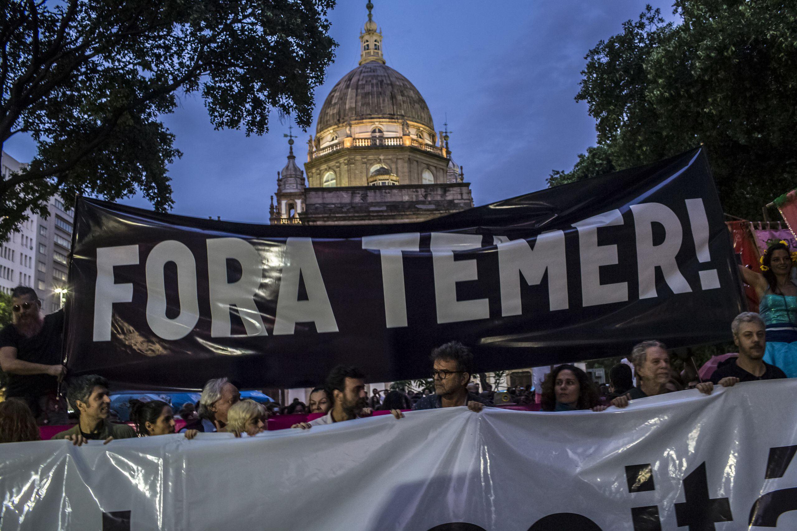 "Protesters hold signs saying ""Temer Out"" in Portuguese to protest the unpopular centrist leader who took power after the impe"