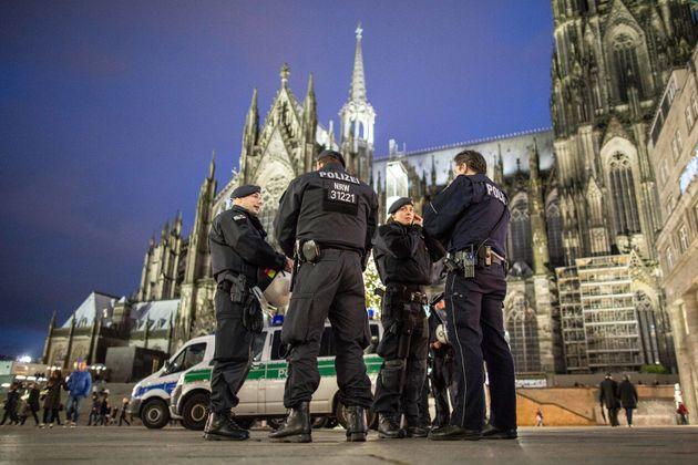 Polizisten stehen vor dem Hauptbahnhof neben dem Kölner Dom.