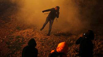 A migrant, part of a caravan of thousands from Central America trying to reach the United States, throws back a tear gas bomb after U.S. Customs and Border Protection (CBP) throw tear gas to the Mexican side of the fence as they prepared to cross it illegally, in Tijuana, Mexico, January 1, 2019. REUTERS/Mohammed Salem