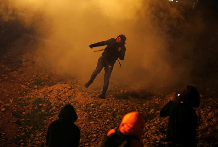 A migrant throws back a tear gas canister launched by U.S. Customs and Border Protection agents into Mexico, near the border