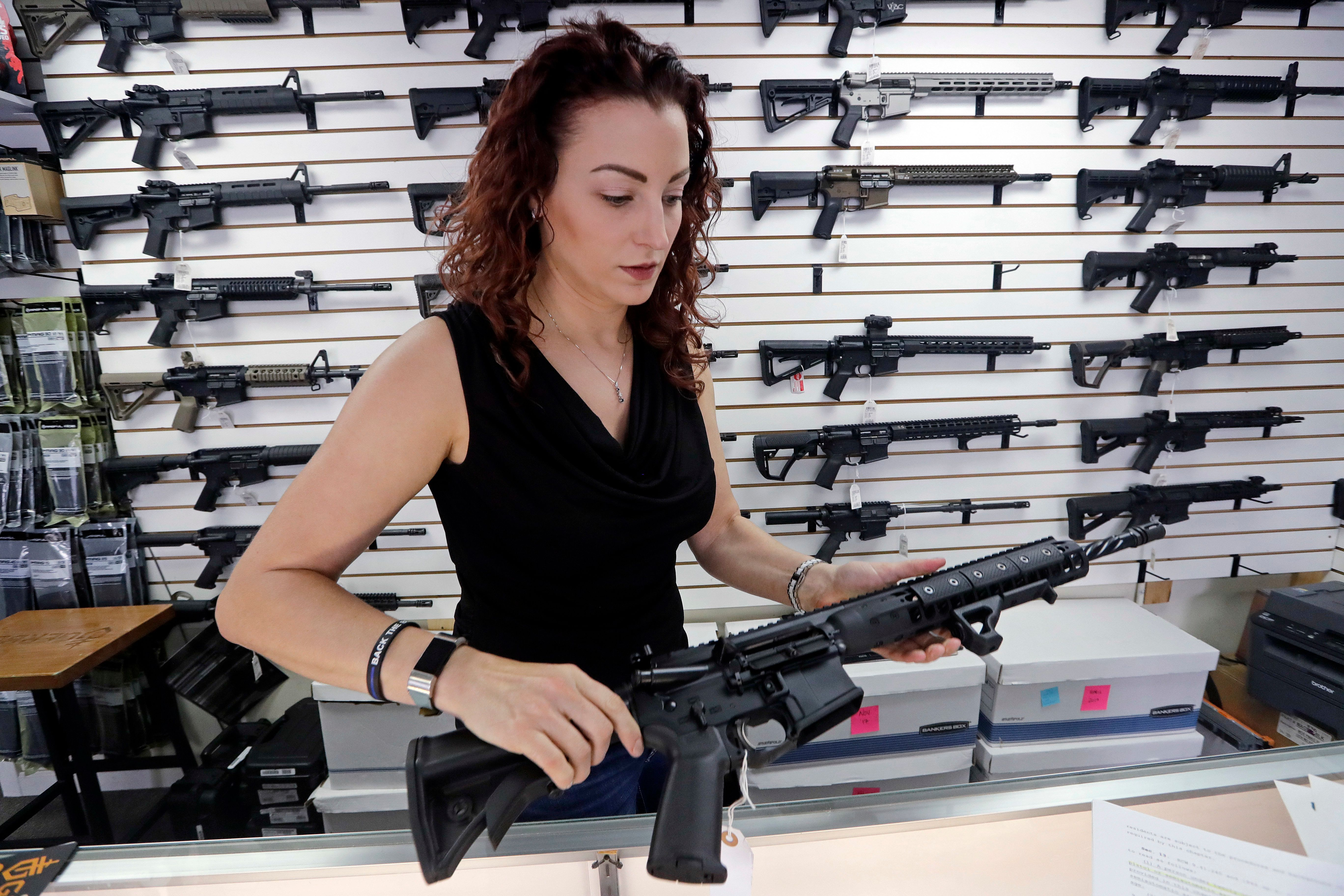 In this photo taken Tuesday, Oct. 2, 2018, gun shop owner Tiffany Teasdale holds a semi-automatic rifle as she talks about a gun initiative on the upcoming ballot, in Lynnwood, Wash. Voters in Washington state will decide the fate of an initiative that seeks to curb gun violence by toughening background checks for people buying semi-automatic rifles, increasing the age limit to 21 for buyers of those guns and requiring safe storage of all firearms. (AP Photo/Elaine Thompson)
