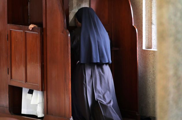 A nun partakes in the sacrament of confession at the Immaculate Heart of Mary Cathedral in Kottayam,...