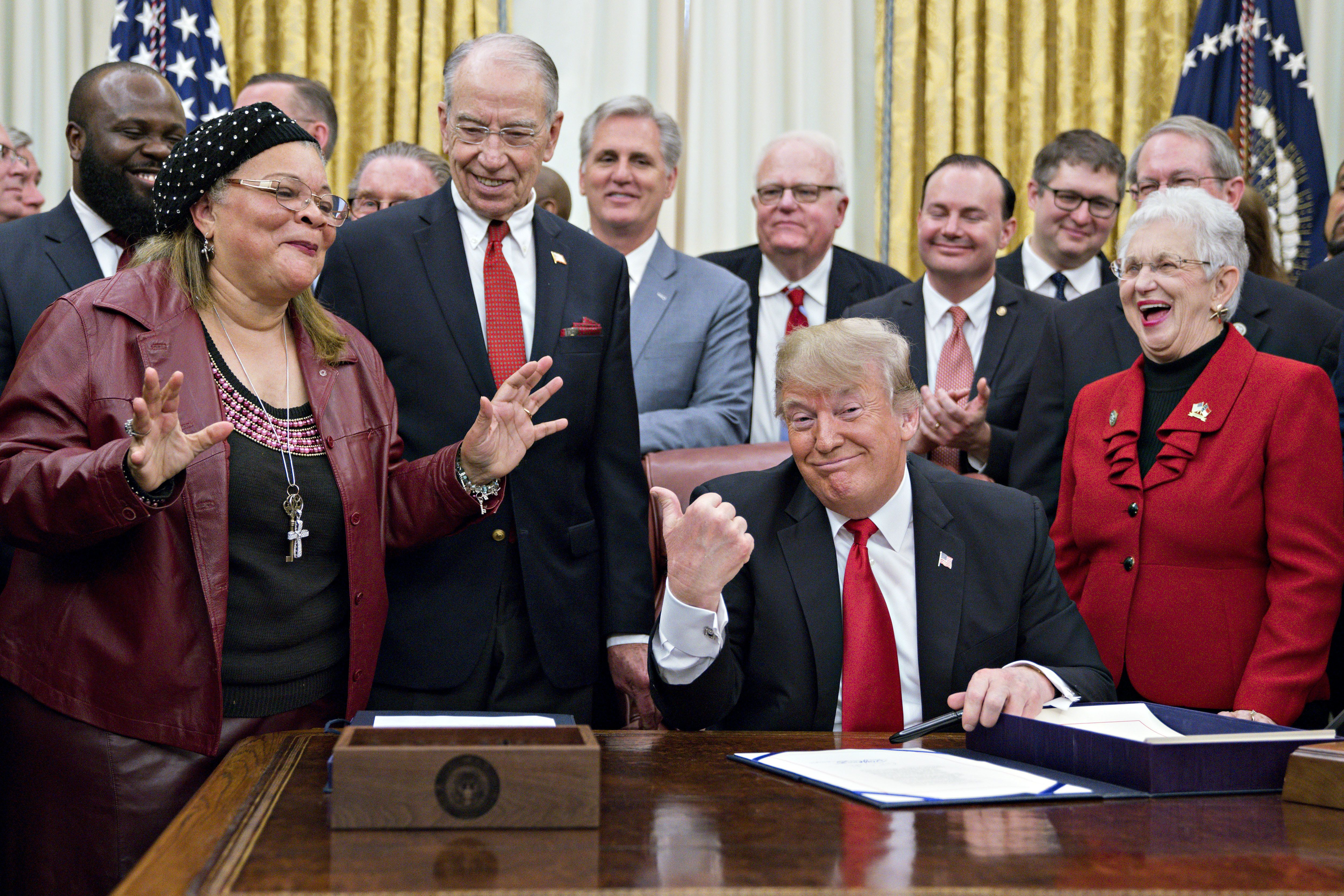 U.S. President Donald Trump, center, gestures as Alveda King, niece of Reverend Martin Luther King Jr., speaks during a signing ceremony for S. 756, First Step Act and H.R. 6964, Juvenile Justice Reform Act with Senator Chuck Grassley, a Republican from Iowa, second left, and Representative Virginia Foxx, a Republican from North Carolina, right, in the Oval Office of the White House in Washington, D.C., U.S., on Friday, Dec. 21, 2018. The U.S. House this week overwhelmingly passed sweeping legislation to replace decades of rigid war-on-crime sentences in the U.S. criminal justice system with more flexible guidelines for judges and aid to nonviolent offenders preparing for life outside prison. Photographer: Andrew Harrer/Bloomberg via Getty Images
