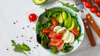 Diet menu, Vegan food. Healthy salad with arugula, Tomatoes, Salmon, Egg and Avocado on a white stone table. Top view flat lay background. Copy space.