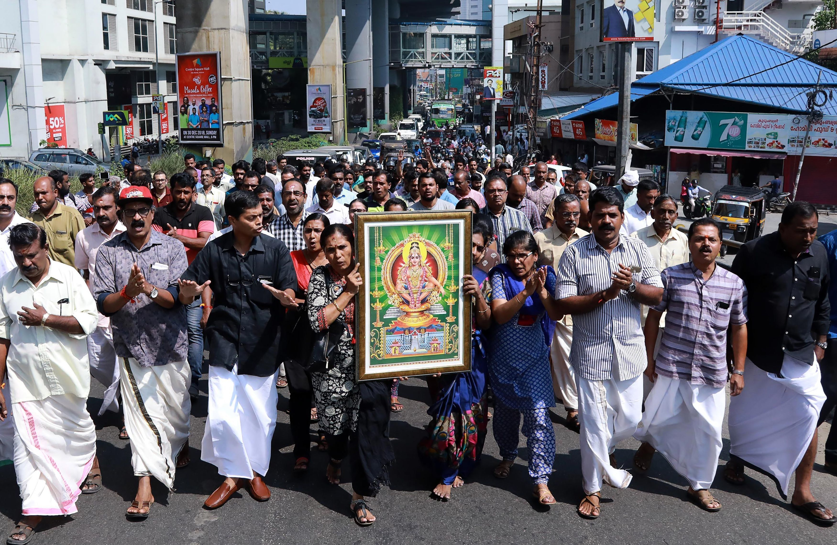 India protesters carry a picture of the Hindu deity Ayyappa at a demonstration following the entry of two women at the Sabarimala temple, in Kochi in southern Kerala state on January 2, 2019. - Two women secretly entered one of Hinduism's holiest shrines on January 2, breaching a blockade around the Sabarimala temple where devotees have been enraged by an Indian Supreme Court decision to overturn a ban on women aged between 10 and 50. (Photo by - / AFP)        (Photo credit should read -/AFP/Getty Images)