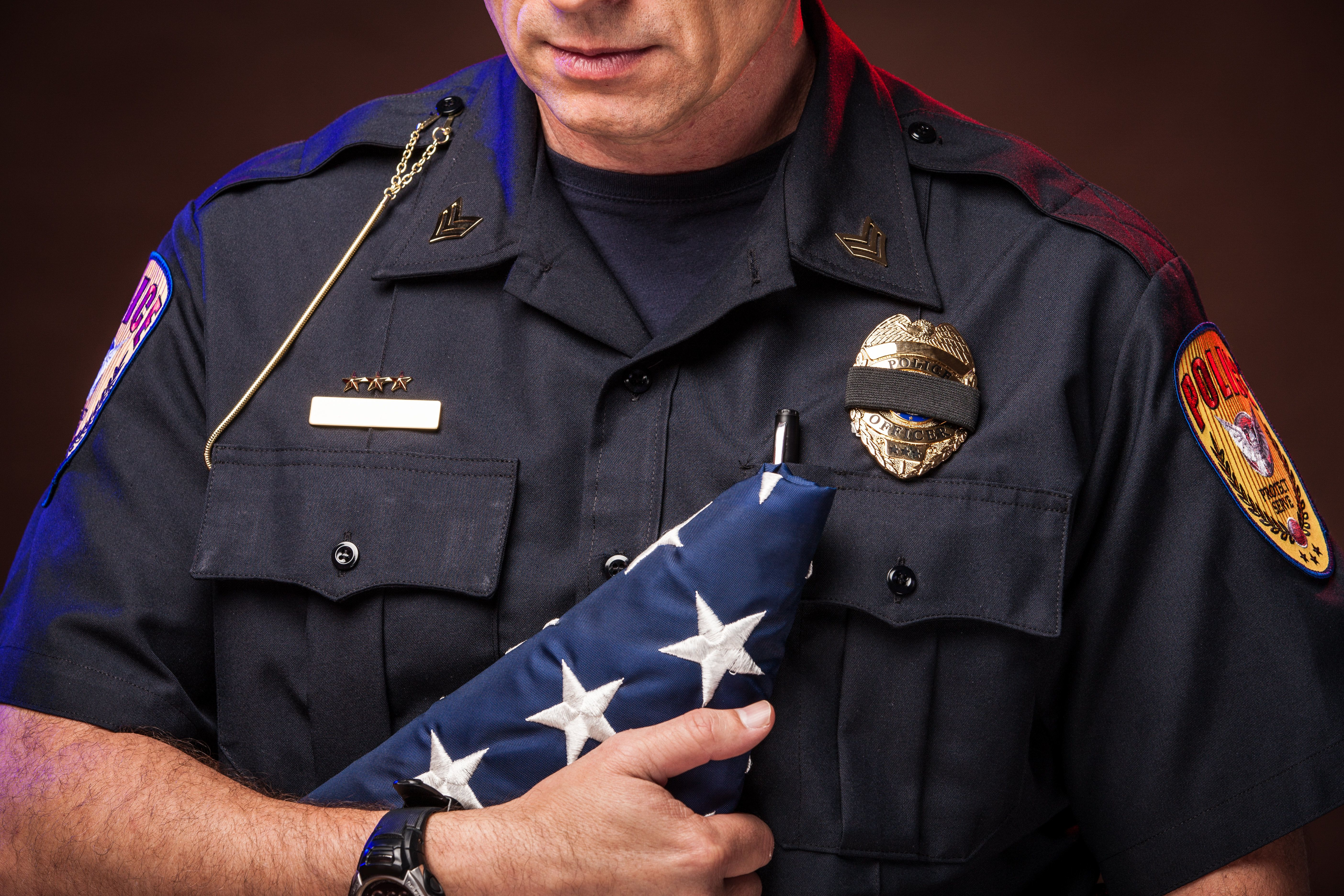 An authentic police officer in dark, moody lighting. Closeup of a male officer in uniform, holding a folded U.S. flag and looking down in respect, sorrow, and honor for a fallen comrade. A black band covers his badge to signify mourning the death of a fellow officer.