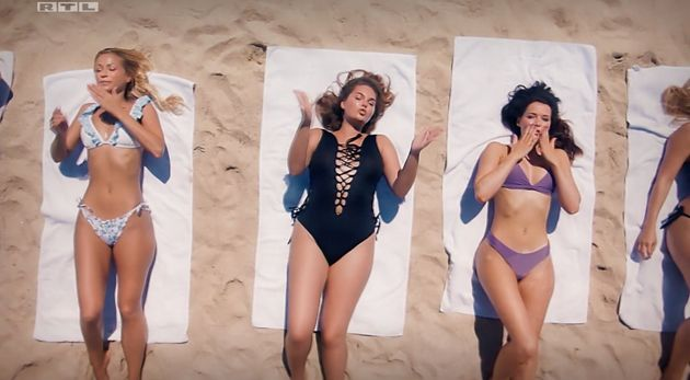 Die Frauen räkeln sich aufgereiht in knappen Outfits am Strand.