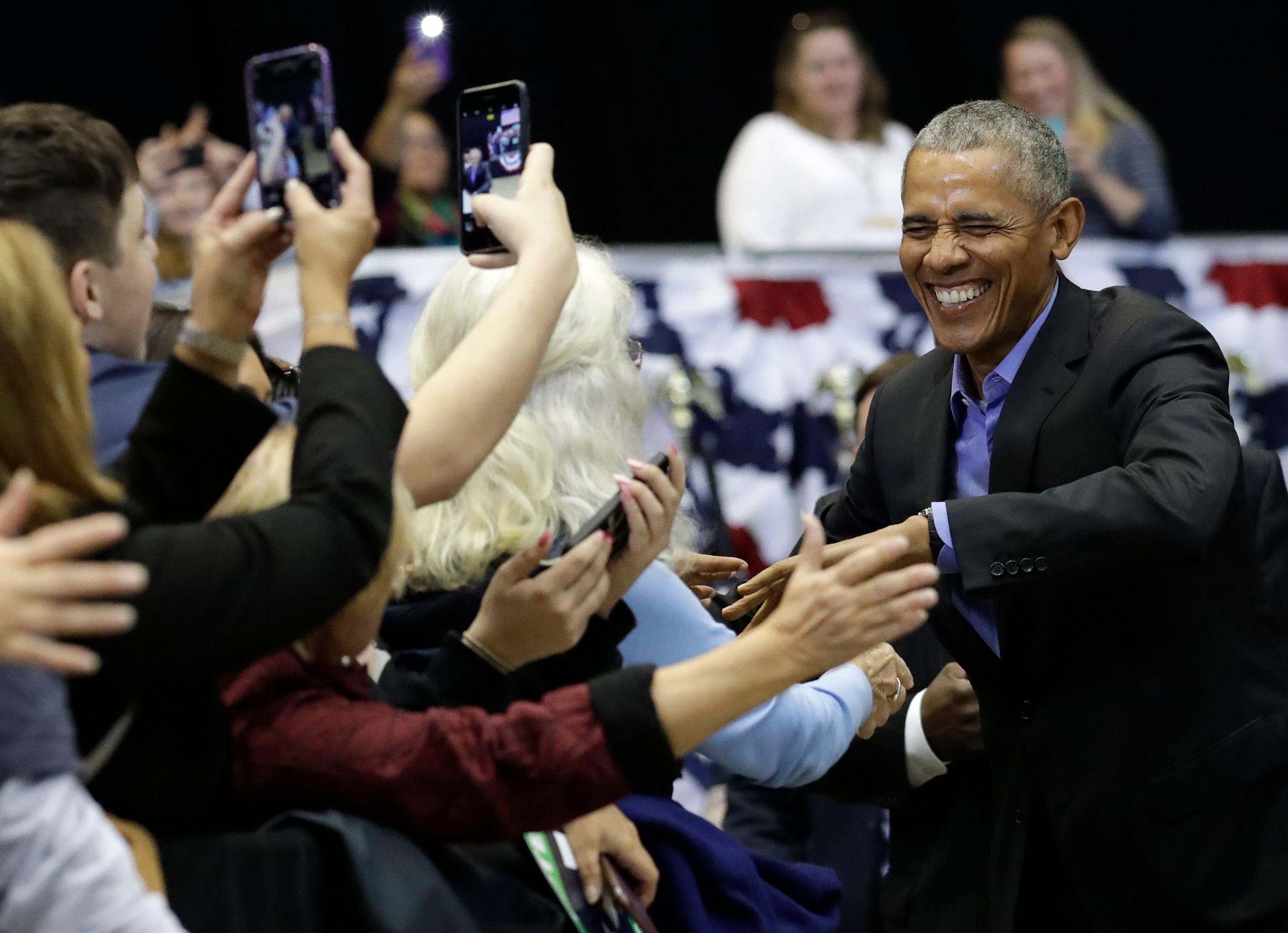 Former President Barack Obama, right, greets Democratic supporters at Genesis Convention Center, Sunday, Nov. 4, 2018, in Gary, Ind. Obama rallied Democrats on behalf of Sen. Joe Donnelly, D-Ind., who faces a stiff challenge from Republican businessman Mike Braun. (AP Photo/Nam Y. Huh)