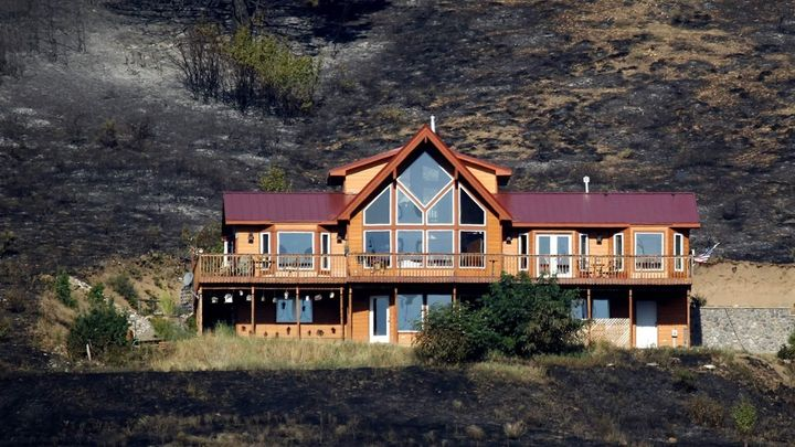 A house stands after surviving a wildfire near Cle Elum, Washington. The house had defensible space around the structure, suc