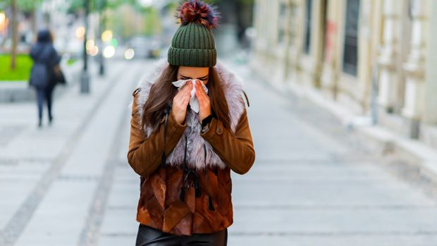 Photo of young Woman standing on the street blowing her nose. Healthcare, flu and people concept - Ill woman blowing nose to paper napkin with eyes closed.