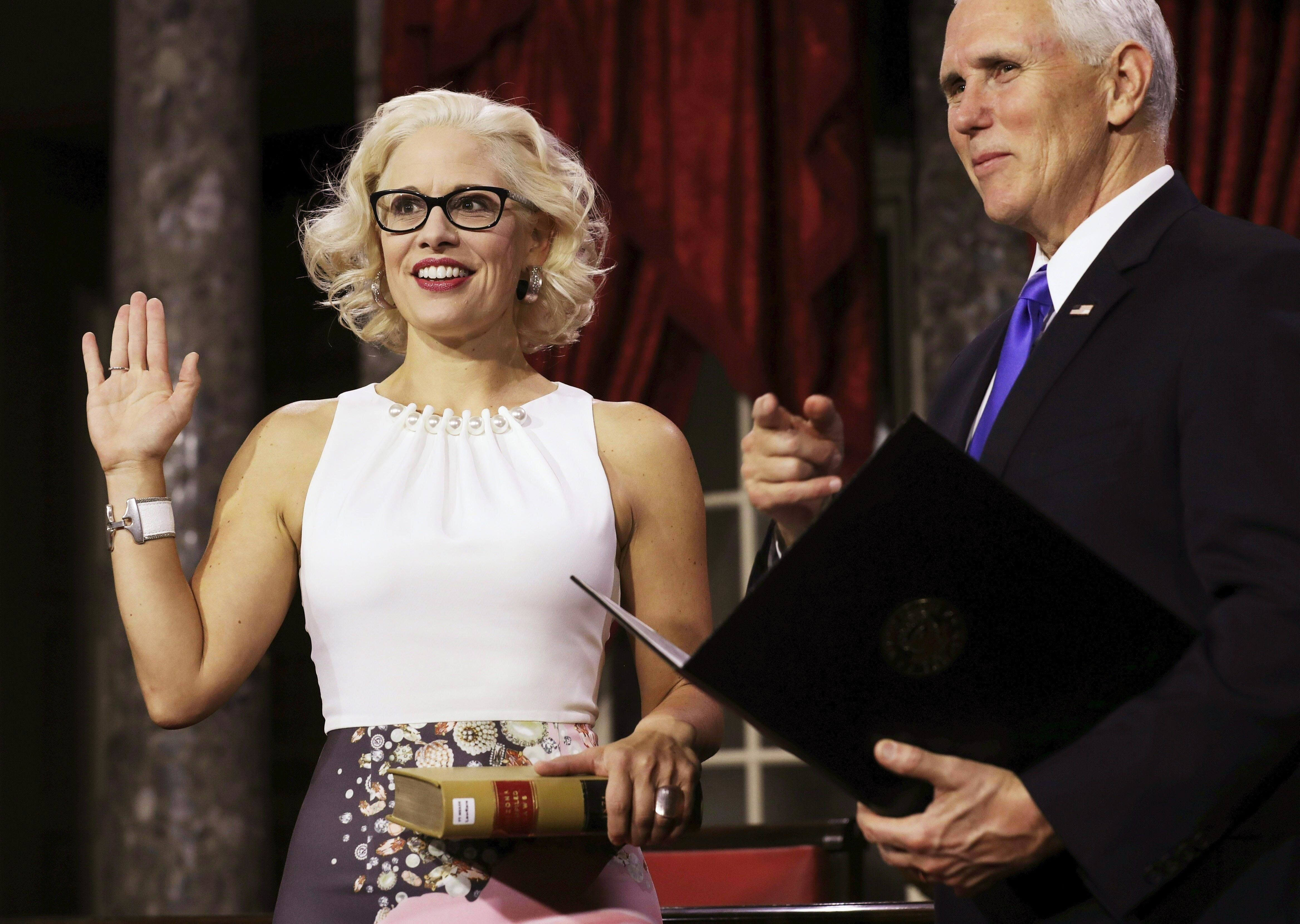 US Senator from Arizona (D) Kirsten Sinema holds a lawbook as she is sworn in by Vice President Mike Pence during the swearing-in re-enactments for recently elected senators in the Old Senate Chamber on Capitol Hill in Washington, DC January 3, 2019. (Photo by Alex EDELMAN / AFP)        (Photo credit should read ALEX EDELMAN/AFP/Getty Images)
