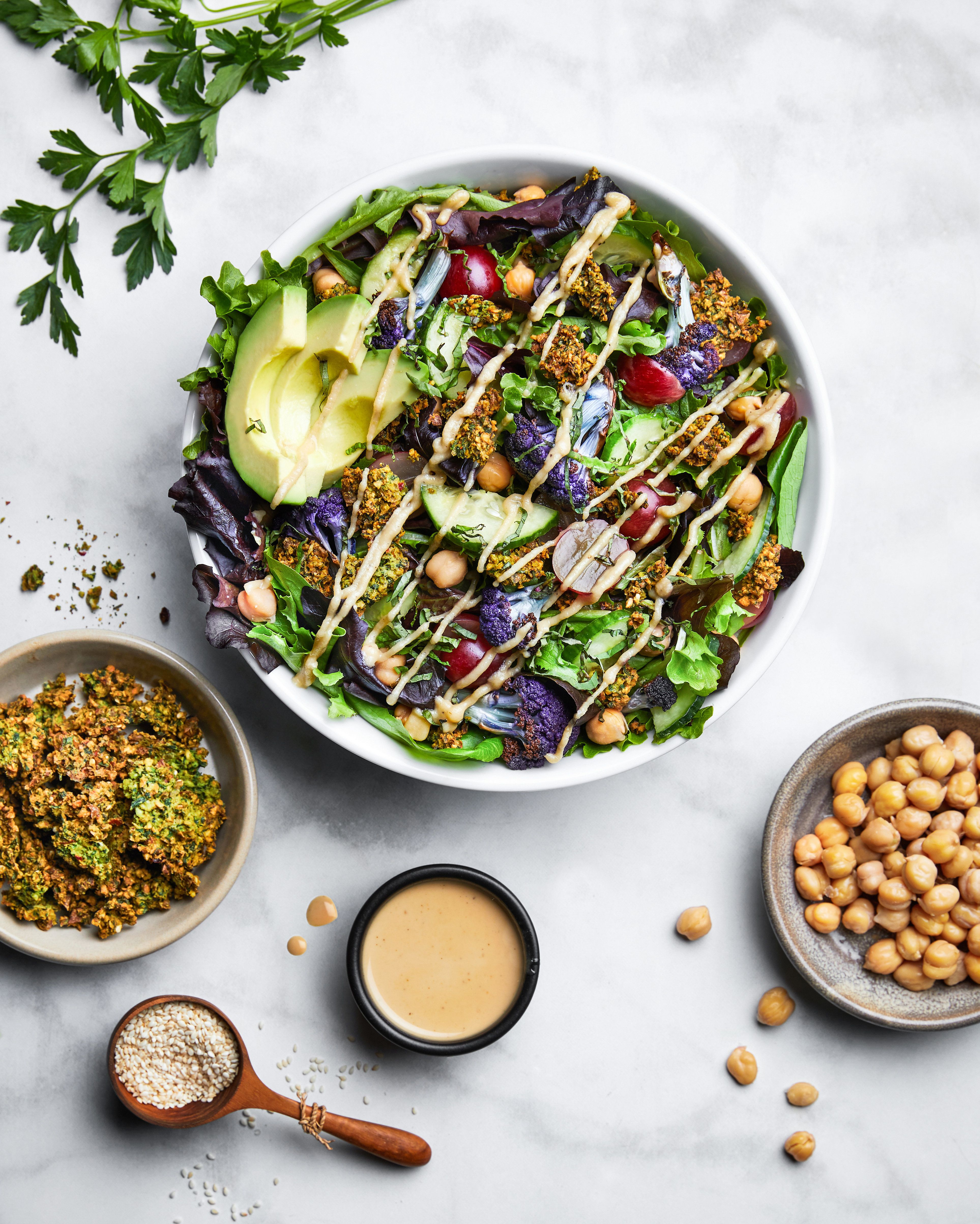 The Falafsalad at Mixt is made with mixed greens, house-baked falafel crumbles, roasted cauliflower, avocado, red flame grapes, cucumbers, chickpeas, fresh herbs and lemon tahini vinaigrette.