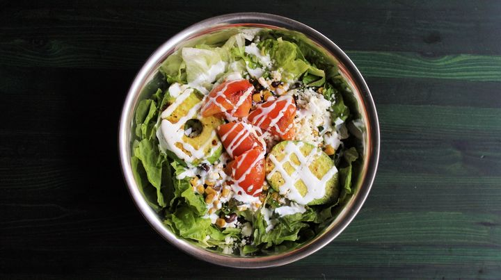 The grilled avocado salad at Snappy Salads is made with red leaf and iceberg lettuce;black bean, poblano and corn relish; grilled avocado and thick-sliced tomato; queso fresco; chipotle-lime vinaigrette; and crema.
