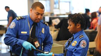 LONG BEACH, CA - JANUARY 24: After frisking a traveler, TSA agent Otwanna Matthews, right, has her latex gloves swabbed by fellow agent Ian Connor at Long Beach Airport on Friday, January 24, 2014. After swabbing the gloves with a cloth, the cloth is then analyzed by a machine that will detect for chemicals or other materials used to make bombs.  (Photo by Scott Varley/Digital First Media/Torrance Daily Breeze via Getty Images)