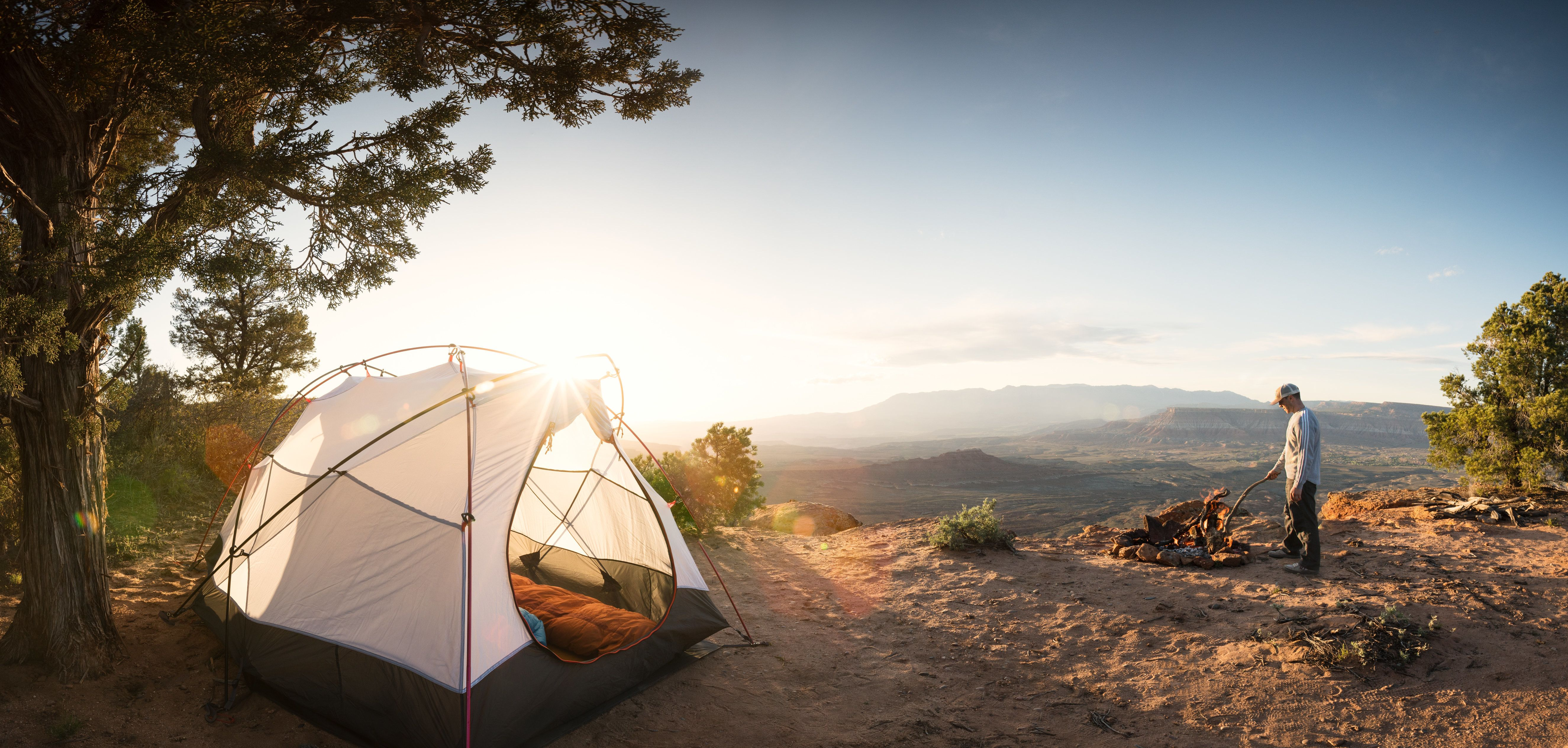 White, domed backpacking tent and down sleeping bag in foreground, where a solitary man wearing teeshirt, long pants and baseball cap stands near his campfire, stirring the coals with a stick. The campsite overlooks a broad desert valley. A pinion pine offers shelter for the tent. Anything could happen on this day primed for adventure.
