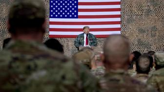 FILE - In this Dec. 26, 2018, file photo, President Donald Trump speaks to members of the military at a hangar rally at Al Asad Air Base, Iraq. President Donald Trump tells troops serving in Iraq that he got them their first pay raise in 10 years and it's a big one. No, and not exactly. (AP Photo/Andrew Harnik, File)