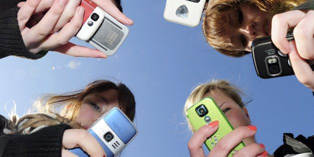 Teenagers use their mobile phones after school time in Vaasa, Finland, on March 30, 2010.    AFP PHOTO / OLIVIER MORIN (Photo