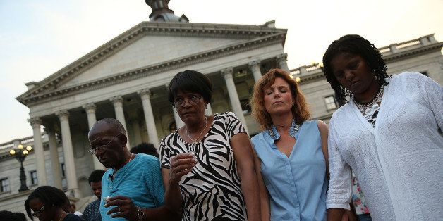 COLUMBIA, SC - JUNE 23:  Participants link arms during a moment of silence at a memorial service for the nine victims of last