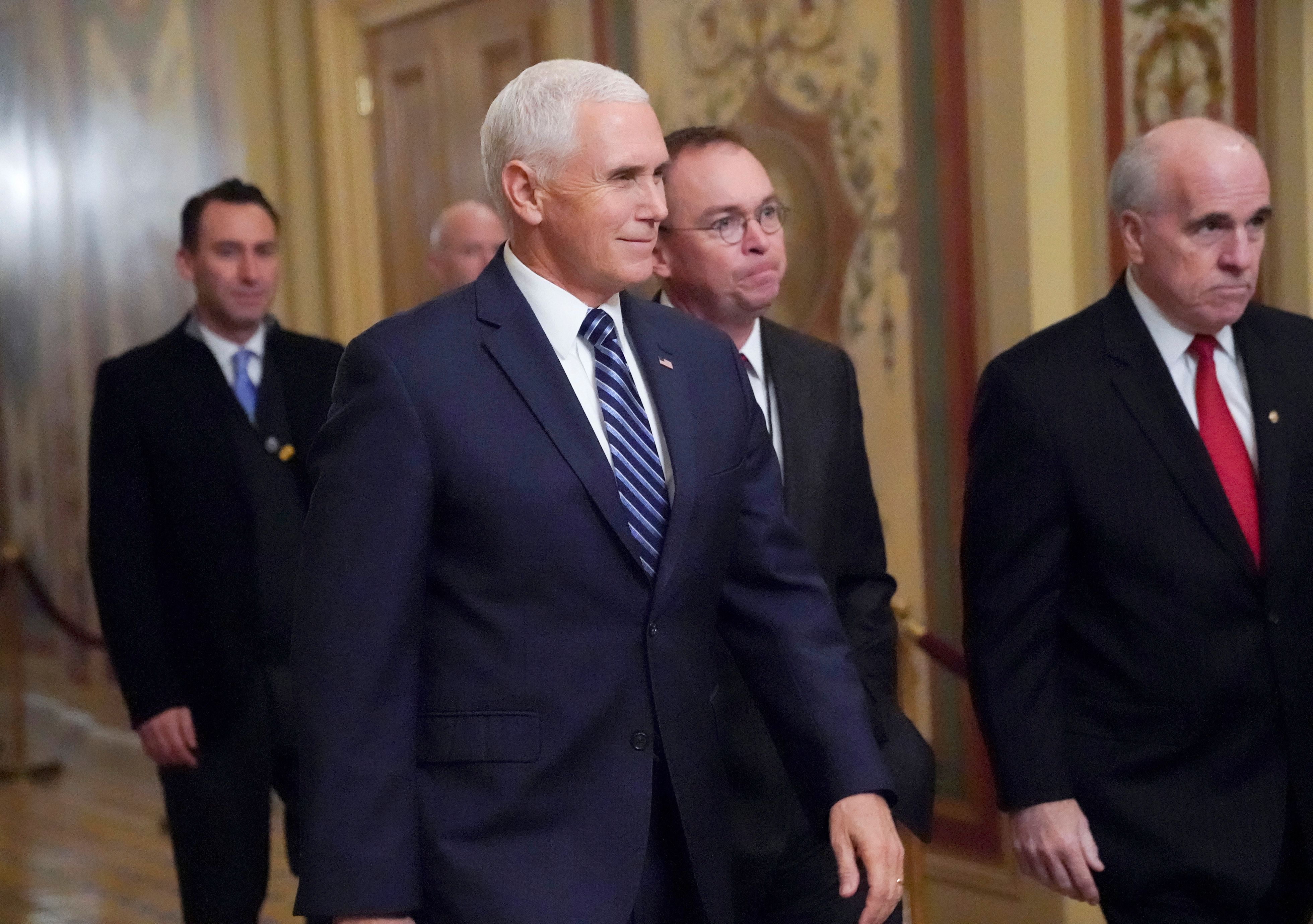 Vice President Mike Pence, center, left, with acting-White House Chief of Staff Mick Mulvaney, center right, arrive at the Capitol as Congress resumes talks on funding without a compromise over money for President Donald Trump's promised wall along the U.S.-Mexico border, in Washington, Saturday, Dec. 22, 2018. (AP Photo/J. Scott Applewhite)