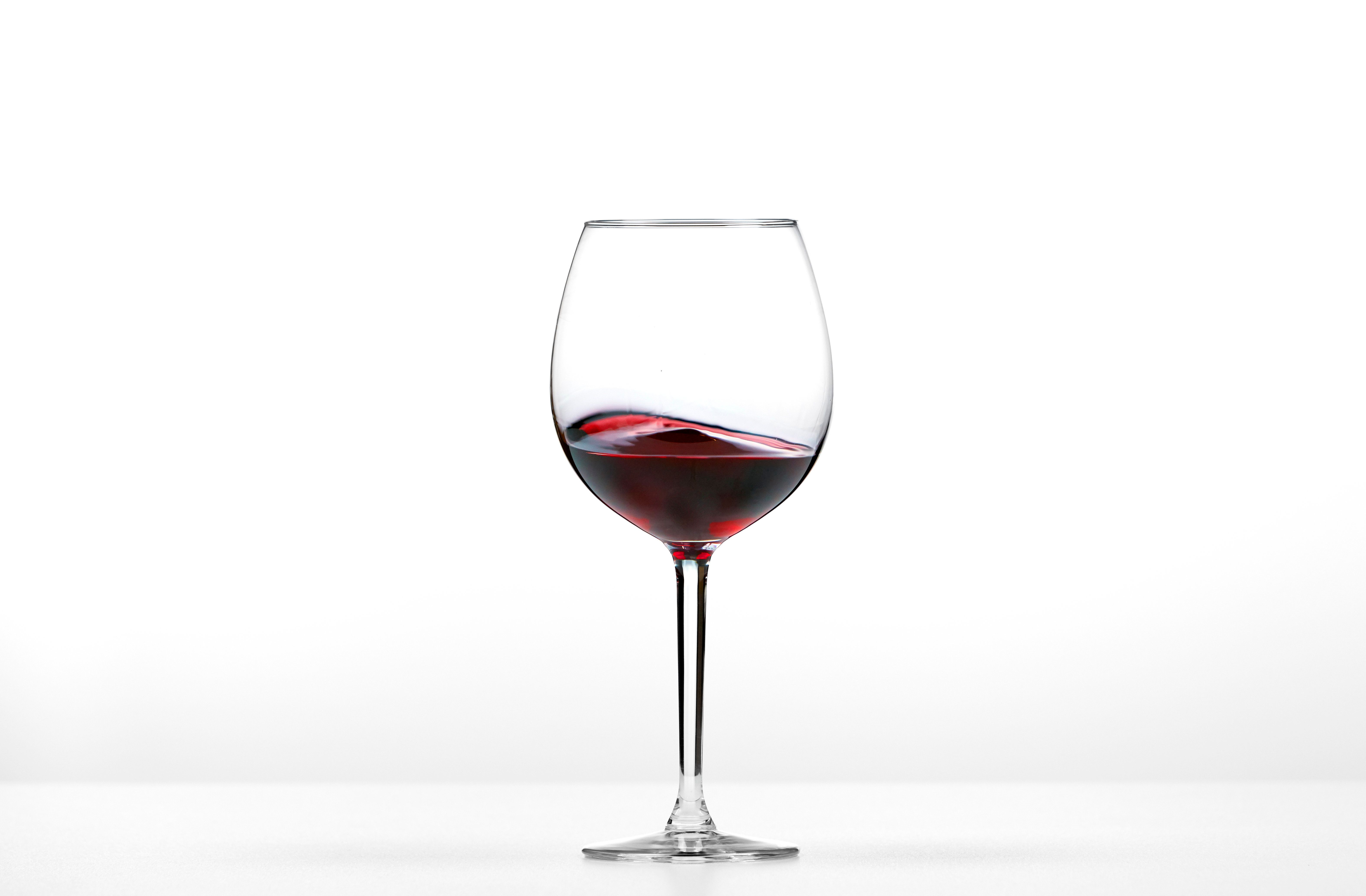 Rolling red wine on white background.
