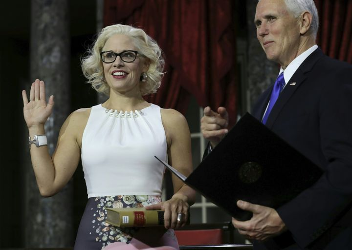 Sen. Kyrsten Sinema (D-Ariz.) holds a law book as she is sworn in by Vice President Mike Pence on Jan. 3 during the swearing-in re-enactments for recently elected senators in the Old Senate Chamber in Washington.