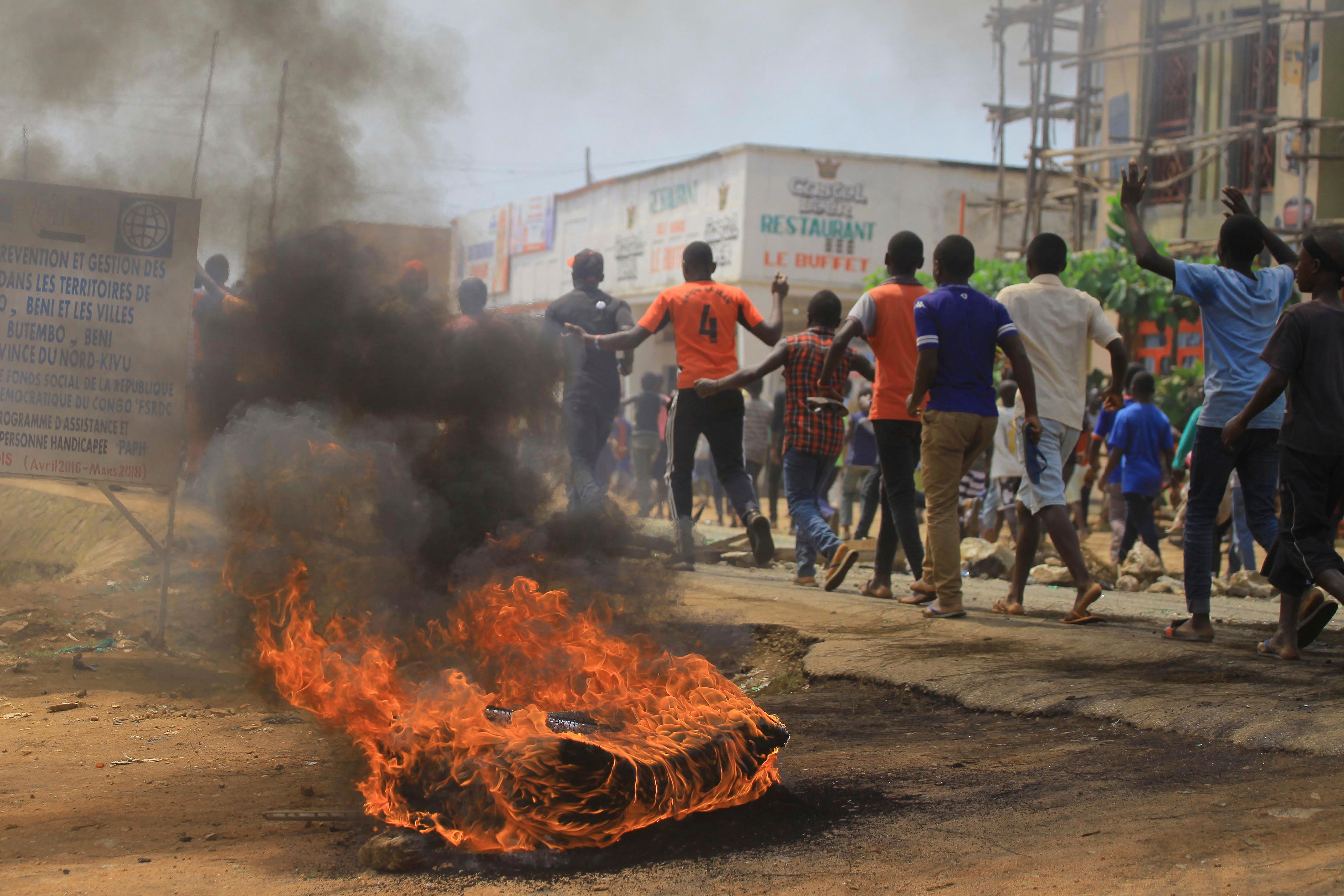 Protesters walk past a burning tyre in the Eastern Congolese town of Beni, Friday Dec. 28, 2018, as they demonstrate against the election postponed until March 2019, announced by Congo's electoral commission for Beni residents that is blamed on a deadly Ebola outbreak.  Congo's leader Joseph Kabila has blamed a deadly Ebola virus outbreak for the last-minute decision to keep an estimated 1 million voters from the polls in Sunday's long-delayed presidential election. (AP Photo/Al-hadji Kudra Maliro)