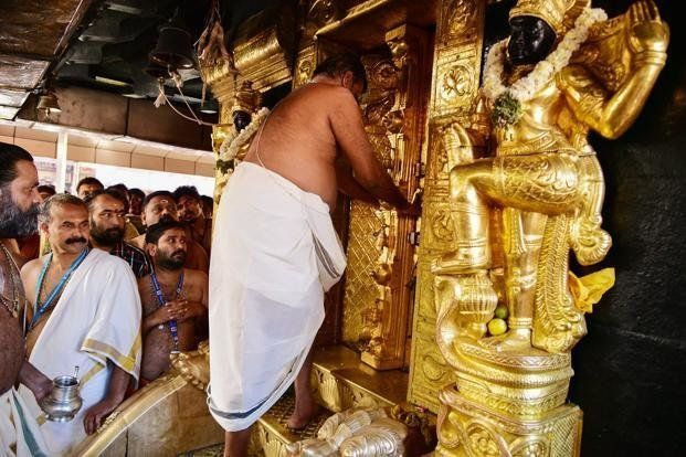 A priest closing doors at the Ayyappa shrine at the Sabarimala temple in Kerala after performing 'purification'...