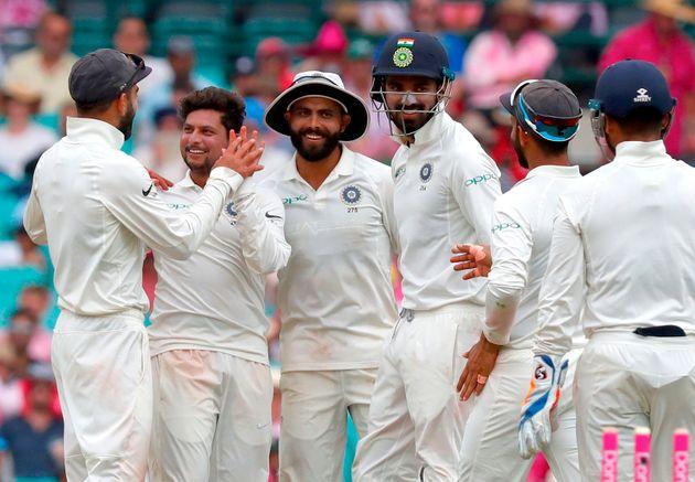 Kuldeep Yadav (2nd L) celebrates with captain Virat Kohli (L) and teammates after dismissing Australia's...