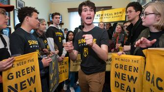 Jeremy Ornstein of Watertown, Mass., center, cheers on fellow environmental activists as they occupy the office of Rep. Steny Hoyer, D-Md., the incoming majority leader, as they try to pressure Democratic support for a sweeping agenda to fight climate change, on Capitol Hill in Washington, Monday, Dec. 10, 2018. (AP Photo/J. Scott Applewhite)
