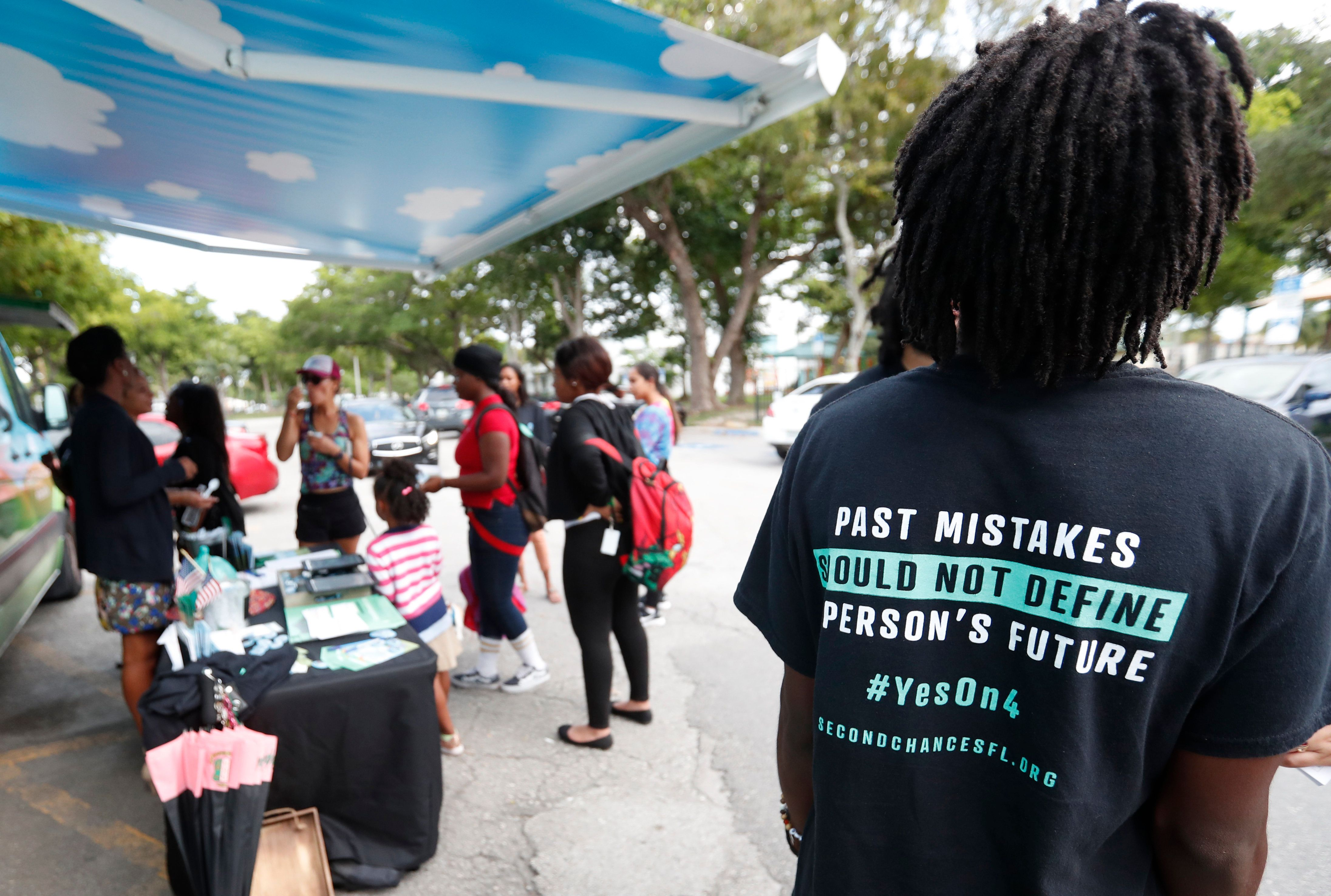 "FILE - In this Oct. 22, 2018 file photo, people gather around the Ben & Jerry's ""Yes on 4"" truck as they learn about Amendment 4 and eat free ice cream at Charles Hadley Park in Miami.  With a single vote Tuesday, Nov. 6, Florida added 1.4 million possible voters to the rolls when it passed Amendment 4, which said that most felons will automatically have their voting rights restored when they complete their sentences and probation. (AP Photo/Wilfredo Lee, File)"