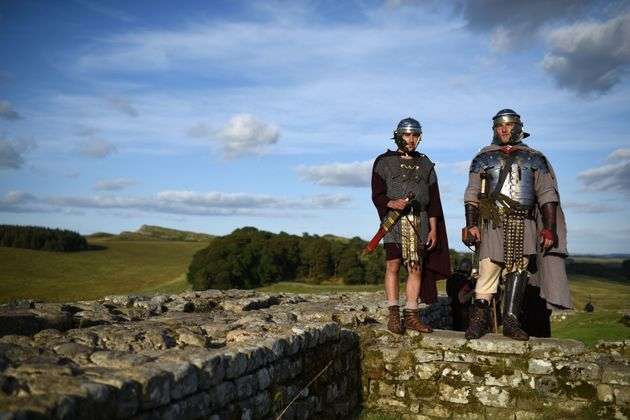 Reenactors portraying soldiers from the Imperial Roman Army stand on Hadrian's Wall at Birdoswald Roman...
