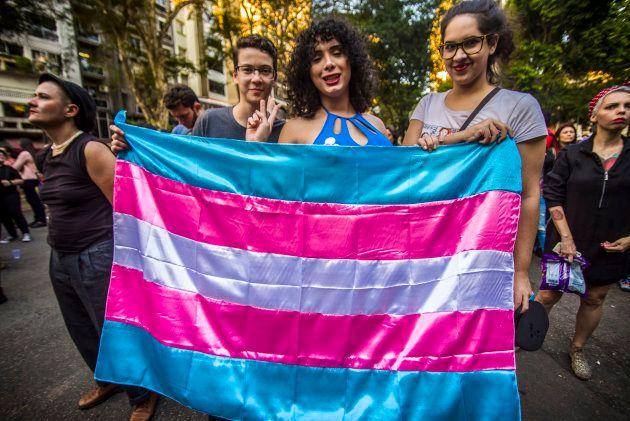 Manifestantes seguram a bandeira do Orgulho Trans em manifestação em São