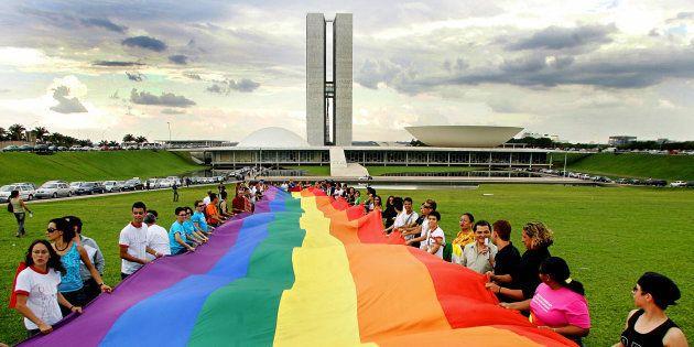 Ativistas ocupam o gramado do Congresso Nacional com a bandeira do arco íris, que representa o movimento...
