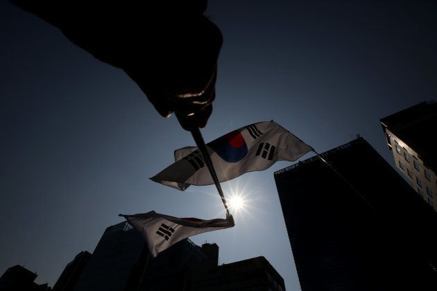 Apoiadores da presidente Park Geun-hy seguram bandeiras do lado de fora do palácio do governo em