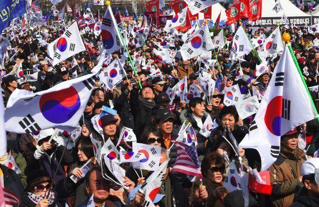 Coreanos que não apoiam o impeachment da presidente Park Geun-Hye seguram bandeiras nacionais durante...