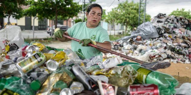 Trabalhadora separa alumínio de lixo em uma cooperativa. Mulheres são maioria em trabalhos