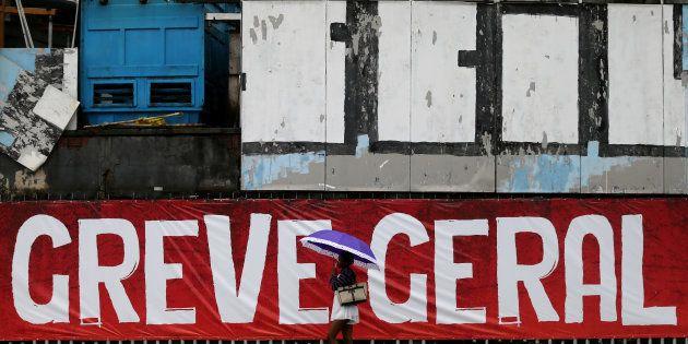 Uma mulher passa em frente ao 'lambe-lambe' que diz 'Greve Geral', no Rio de