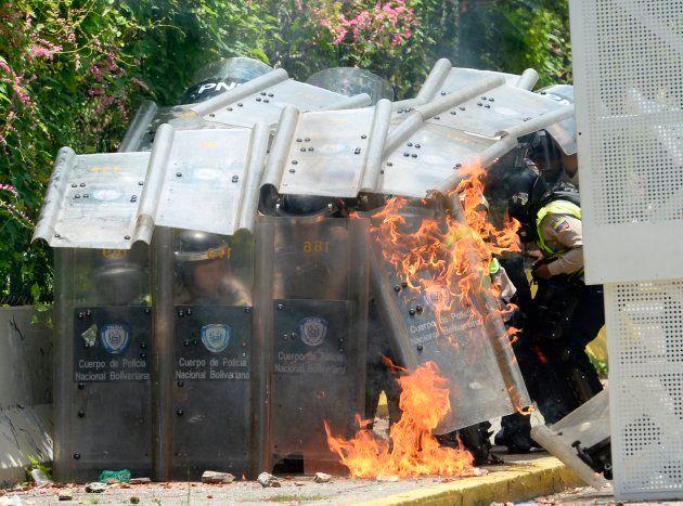 A polícia se protege depois que estudantes jogaram cocotéis molotov durante