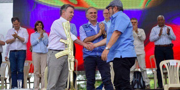 O presidente colombiano Juan Manuel Santos e o líder das Farc Rodrigo Londono celebram o histórico acordo...