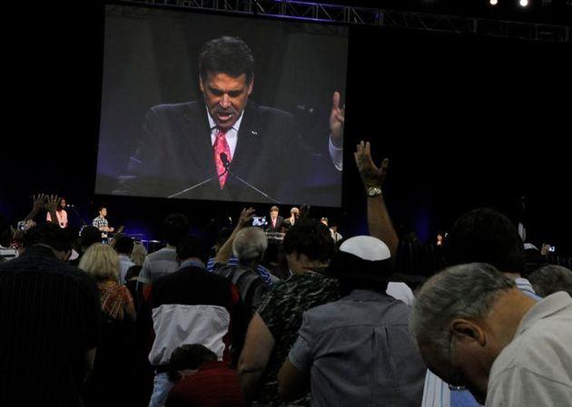 O ex-governador do Texas, Rick Perry, no telão do evento The Response, um dia de orações e jejum, em...