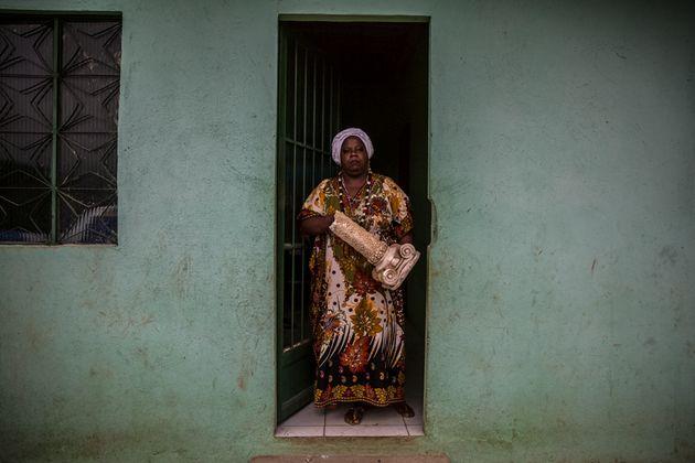 Mãe Vivian na porta da casa em Sepetiba com parte da estrutura da casa de Seropédica em