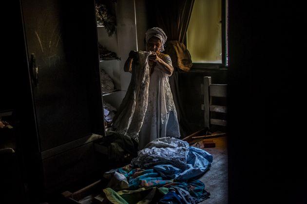 Mãe Merinha olha as roupas de santo