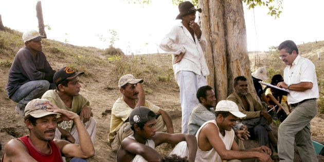 Inspetor do Ministério do Trabalho (dir.) conversa com trabalhadores escravos descobertos na fazenda...