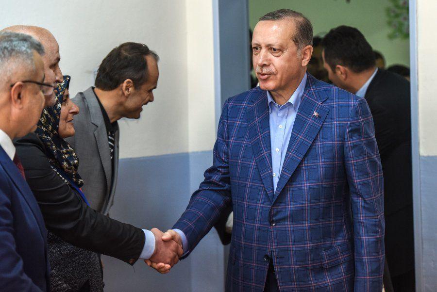 O presidente turco Recep Tayyip Erdogan cumprimenta funcionário ao chegar a um local de votação para...
