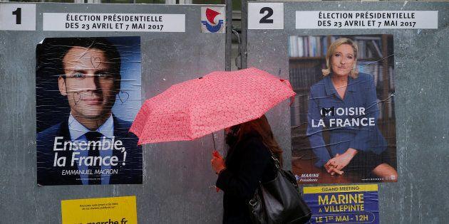 Uma mulher passa à frente de posteres oficiais de Macron e Le Pen para as eleições presidenciais de