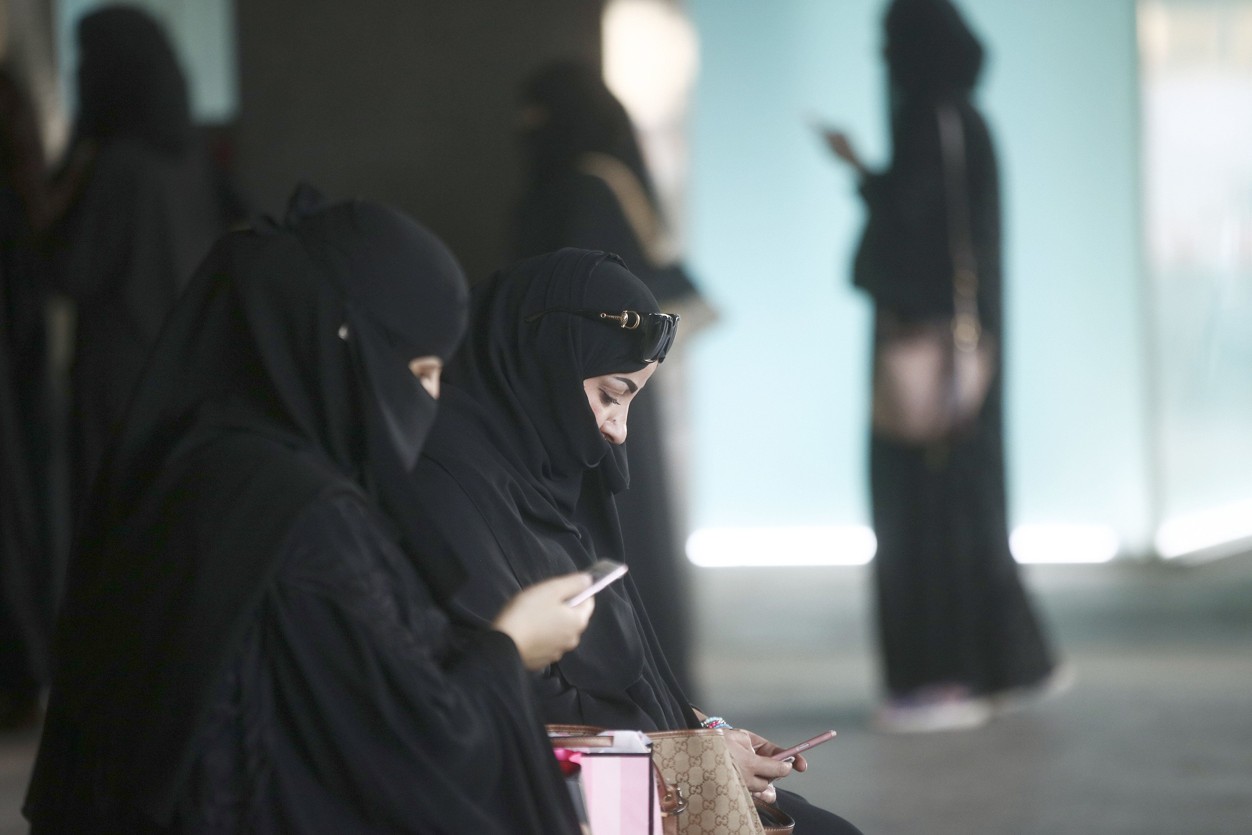 Female shoppers wearing traditional Saudi Arabian dress check their smartphones whilst waiting for transport outside the Tiffany & Co. jewelery store at the Kingdom Centre shopping mall in Riyadh, Saudi Arabia, on Friday, Dec. 2, 2016. Saudi Arabia is working to reduce the Middle Easts biggest economys reliance on oil, which provides three-quarters of government revenue, as part of a plan for the biggest economic shakeup since the countrys founding. Photographer: Simon Dawson/Bloomberg via Getty Images